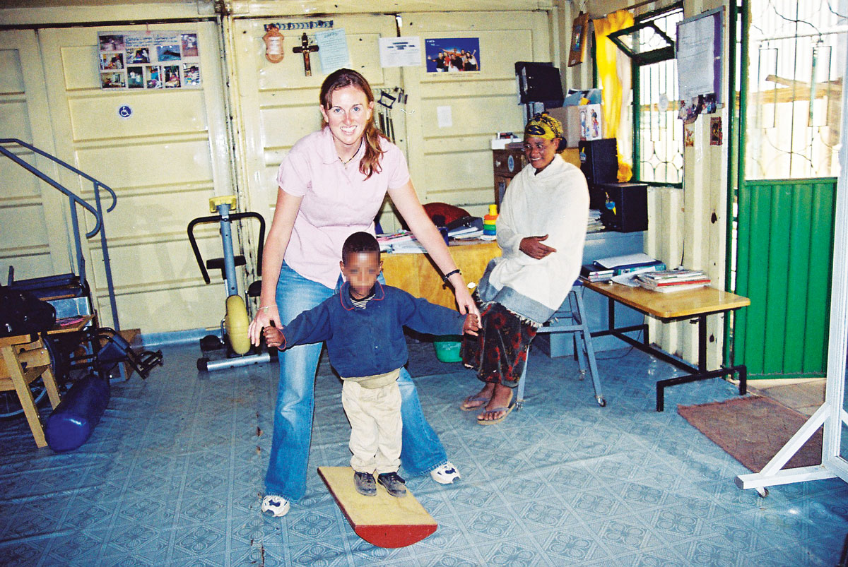 Julie with a paediatric patient in the clinic in Addis Ababa. The patient is standing on a wobble beam, to improve his balance and stability in walking.
